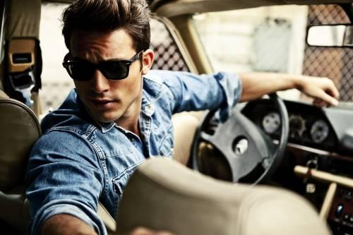Парень в черных очках за рулем автомобиля